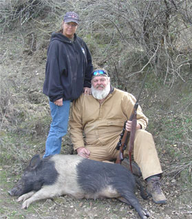 Husband and wife hunters with dutchbelt hog
